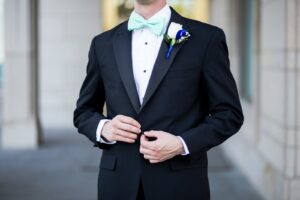 Zoom in of grooms suit and baby blue bowtie.