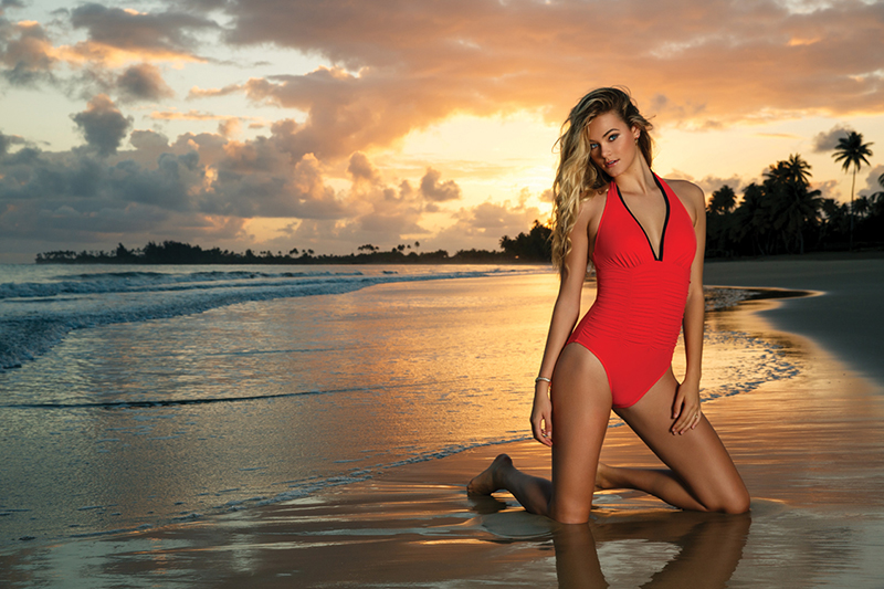 Body contouring, shirring and a deep-V neckline outlined in black makes a romantic beach interlude on a sultry summer evening even hotter! A fiery-red maillot by Magicsuit is shot against a breathtakingly beautiful Hawaiian sunset.