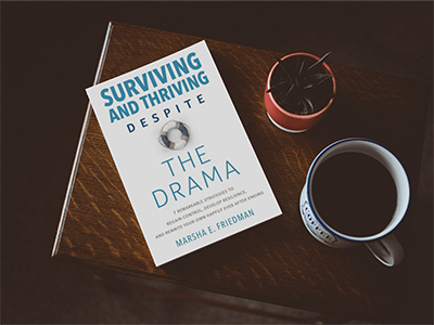 Surviving and Thriving Book on side table with coffee cup and small plant