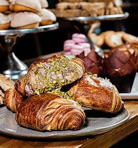 Plate of croissants with other pastries in the background