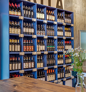 Blue cabinets of bottles of wine available for purchase