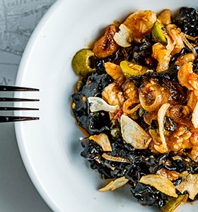 White plate of squid ink pasta with tomatoes and olives
