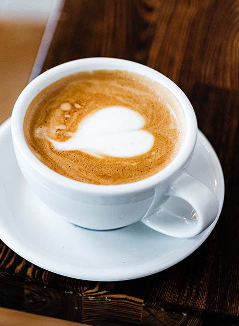 White mug of cappuccino with heart made with the foam