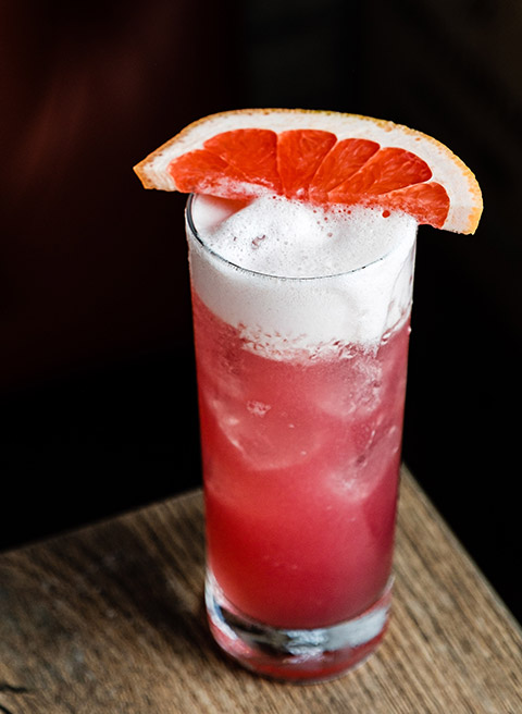 Pink cocktail with slice of grapefruit on top