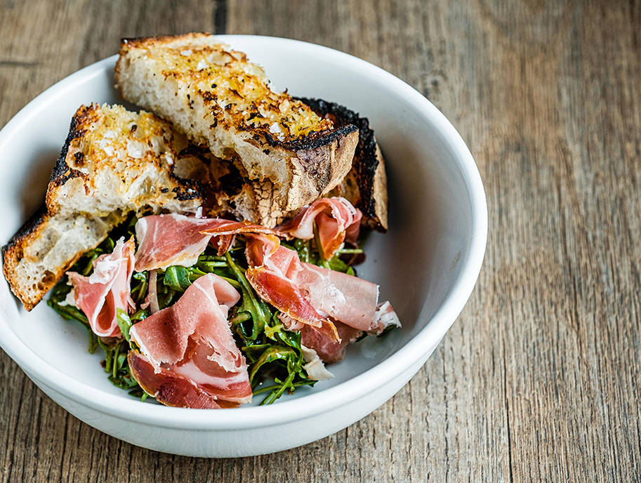 Bowl of prosciutto, greens and toasted breads