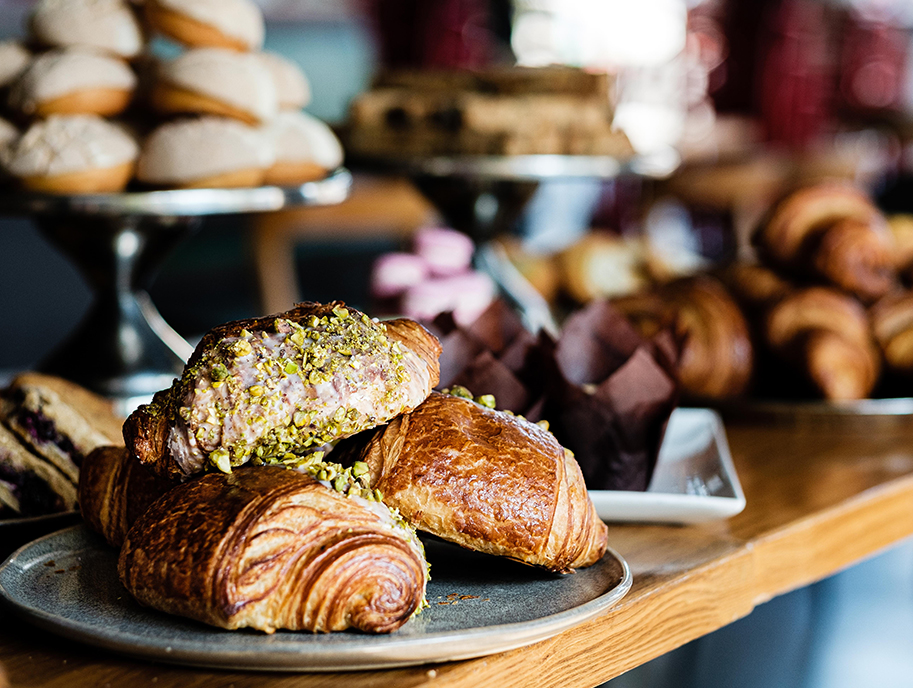 Pistachio croissants and other pastries in the background