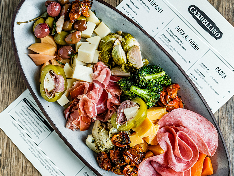 Overview of antipasti plate that includes meats, cheeses, pickled accompaniments and more