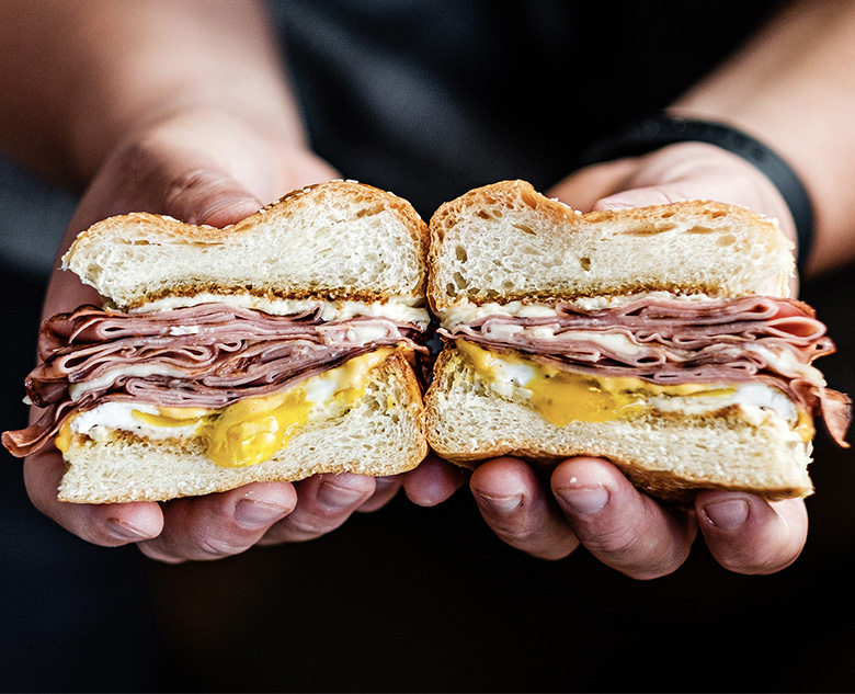 Hands holding meat and egg sandwich cut in half
