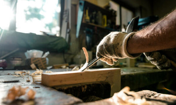 An experienced carpenter shapes wood with a chisel.