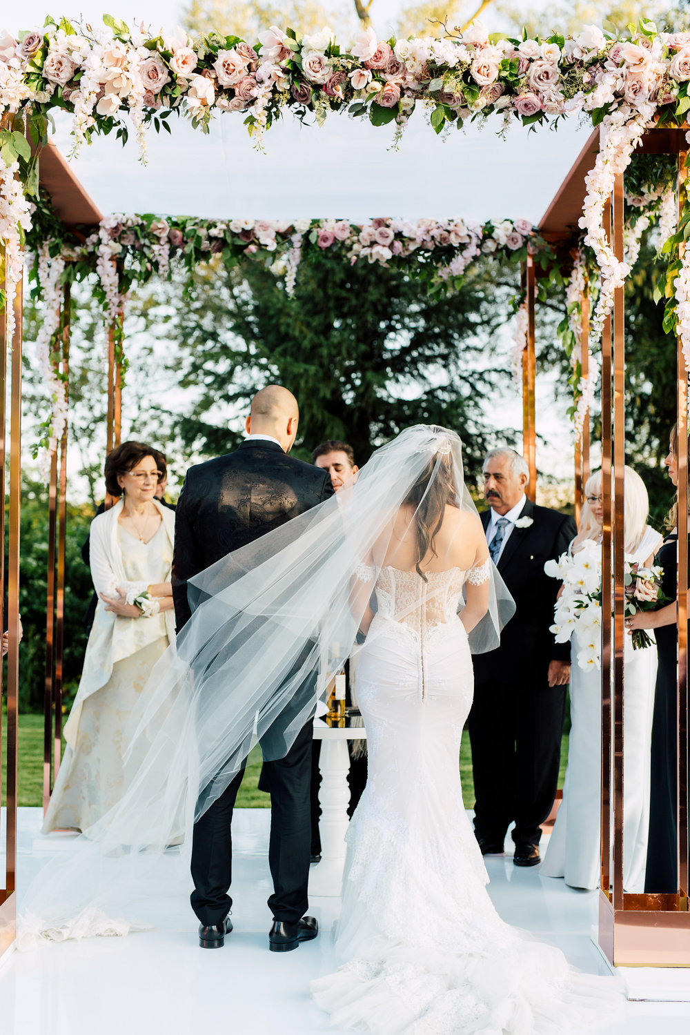 Outdoor wedding ceremony with blush roses archway