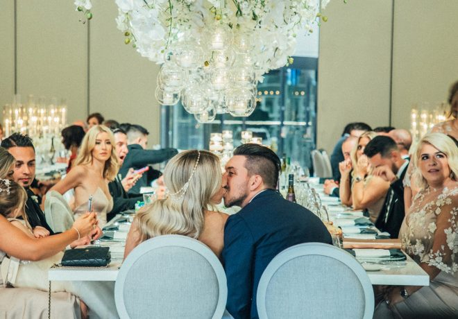 newlyweds kissing at head table