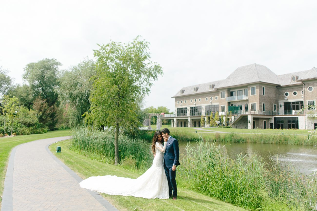 Newlyweds posing by the pond at the Arlington Estate