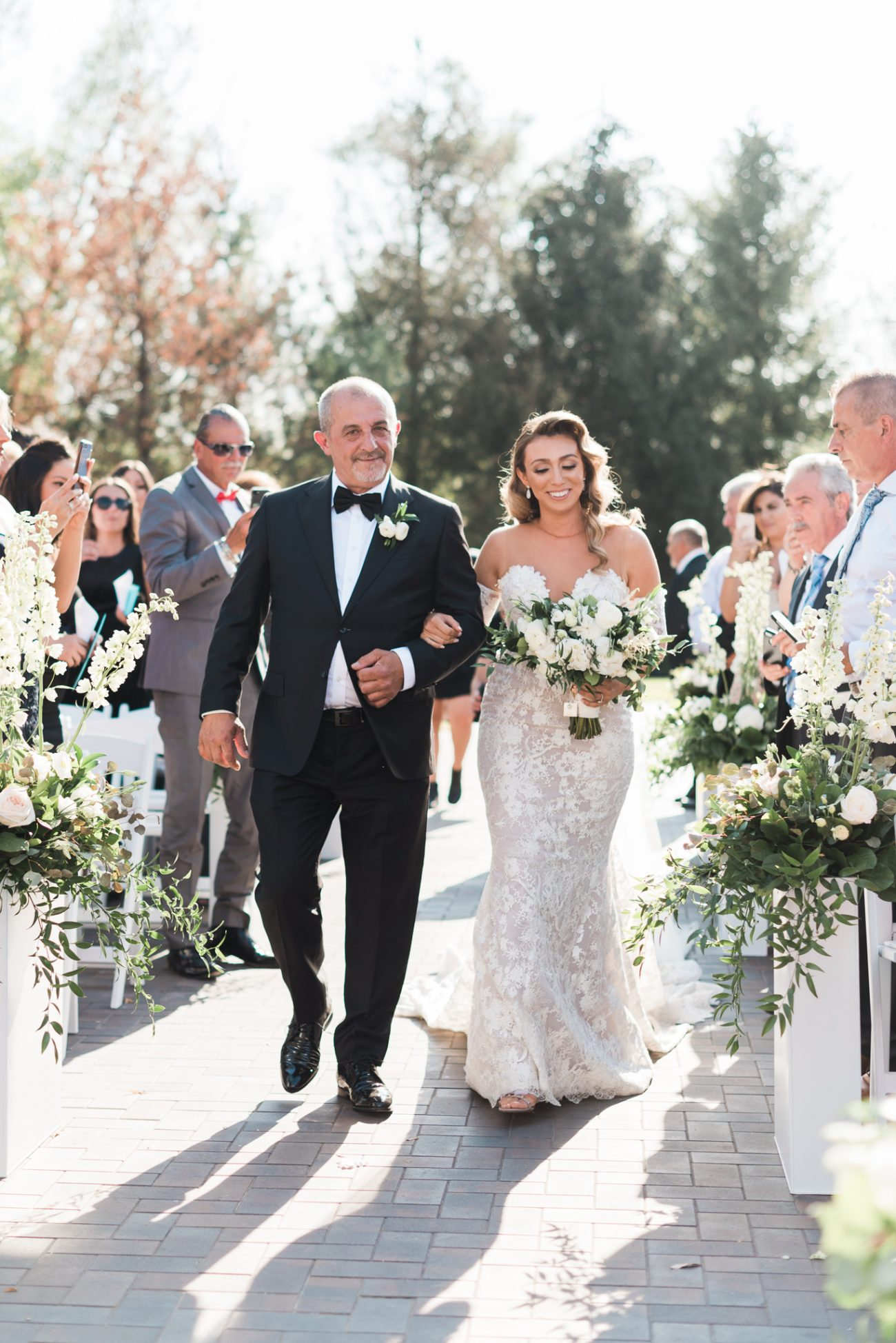 Bride and father walking down the path in outdoor ceremony