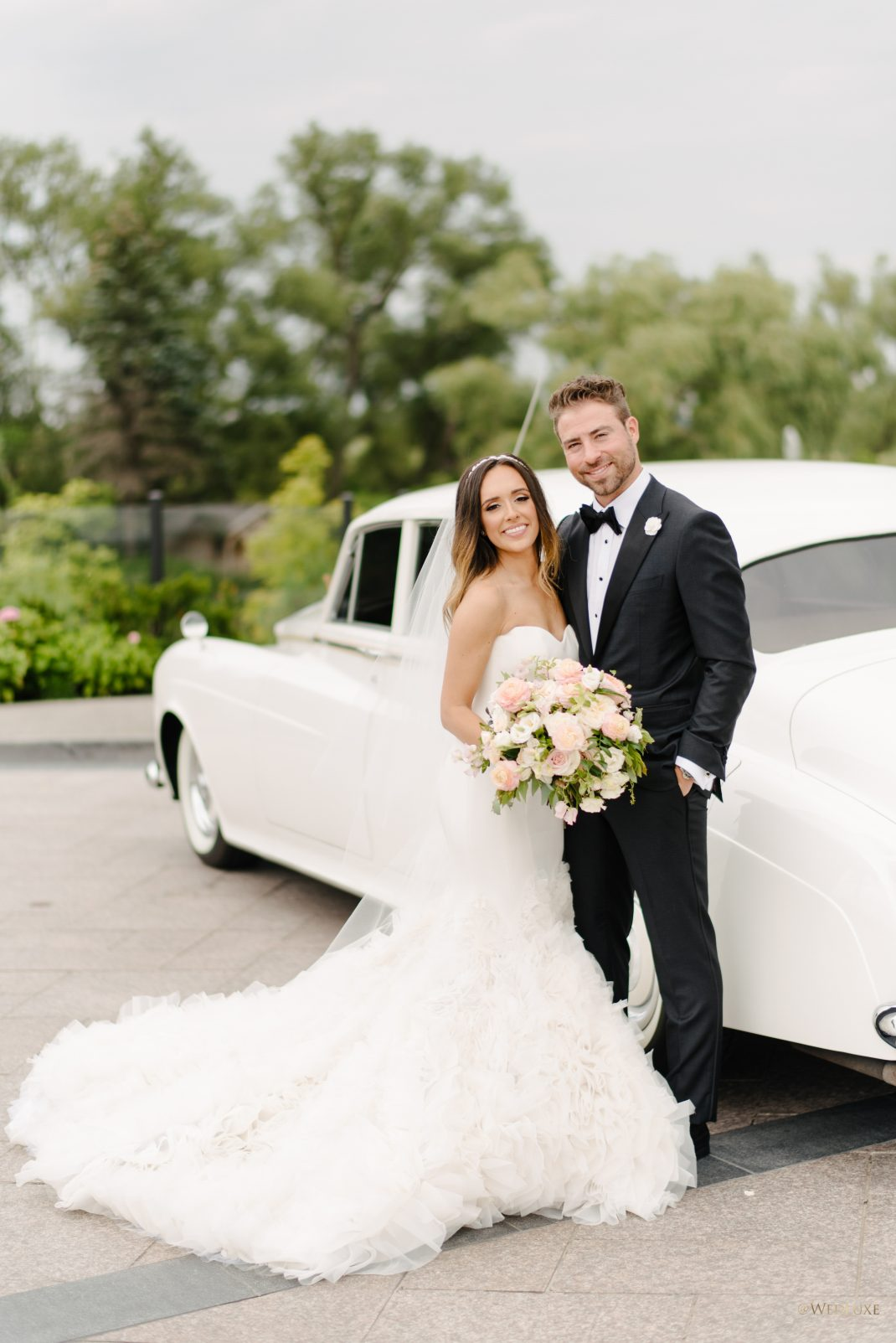Happy Newlyweds outside with limo