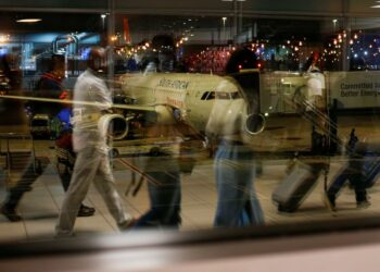 FILE PHOTO: Passengers' reflections are seen in a terminal window with a South African Airways (SAA) plane on the apron at OR Tambo International Airport in Johannesburg, South Africa, February 13, 2020. REUTERS/Rogan Ward