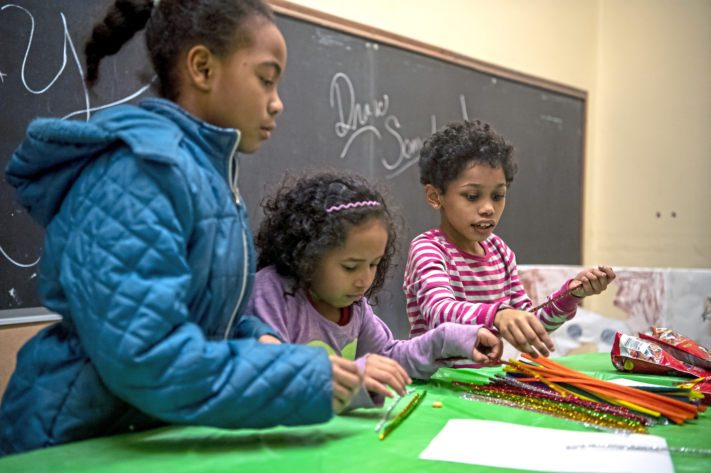 From left, Amy Abraham, 9, Mary Muyango, 7, and Maya Muyango, 8, all of Perry North, play in a room in the old McNaugher school during a holiday party for the Fineview and Perry Hilltop Citizen Councils, Thursday, Dec. 13, 2018, in Perry North. (Alexandra Wimley/Post-Gazette)