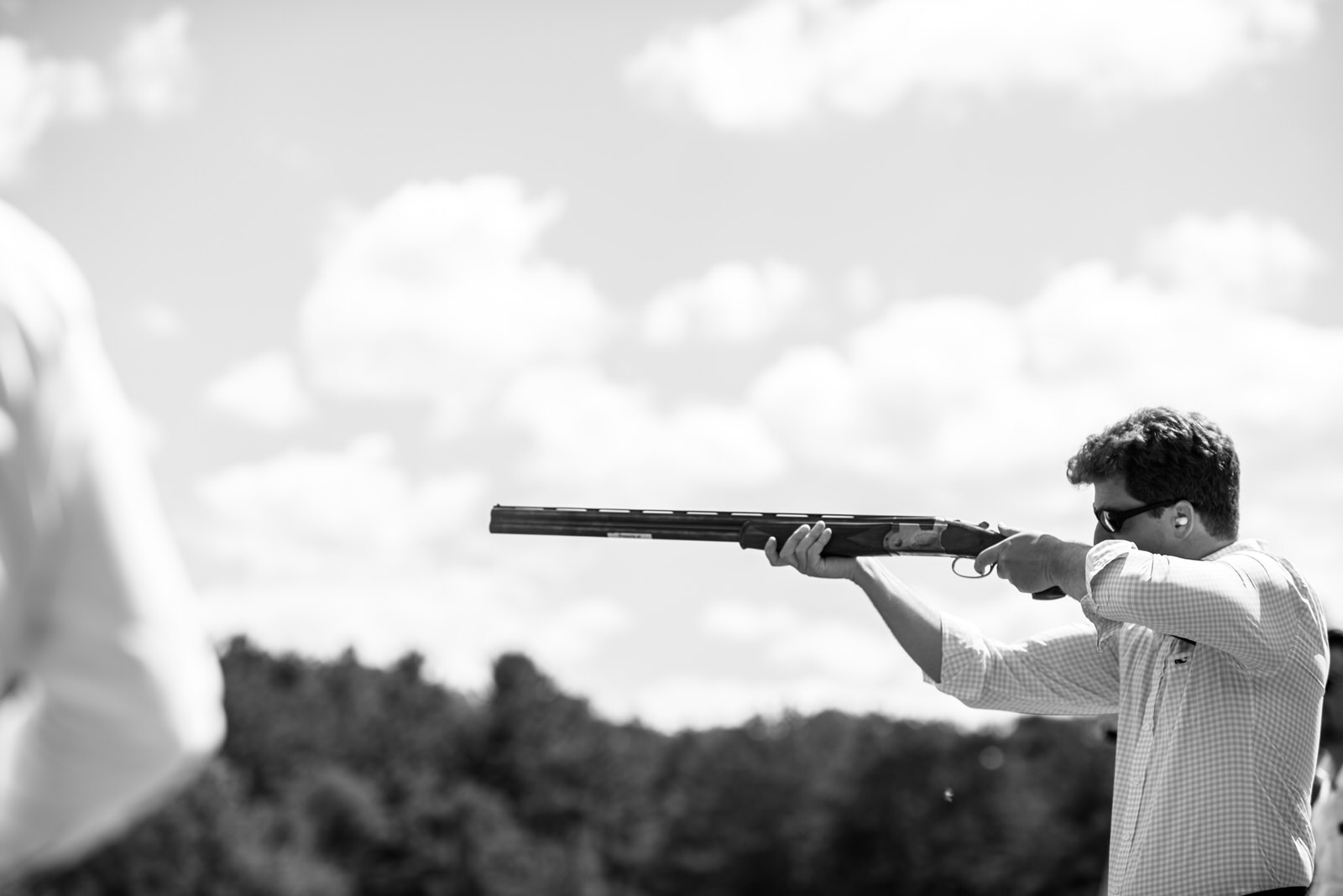 Groom shooting shotgun at Country Club wedding