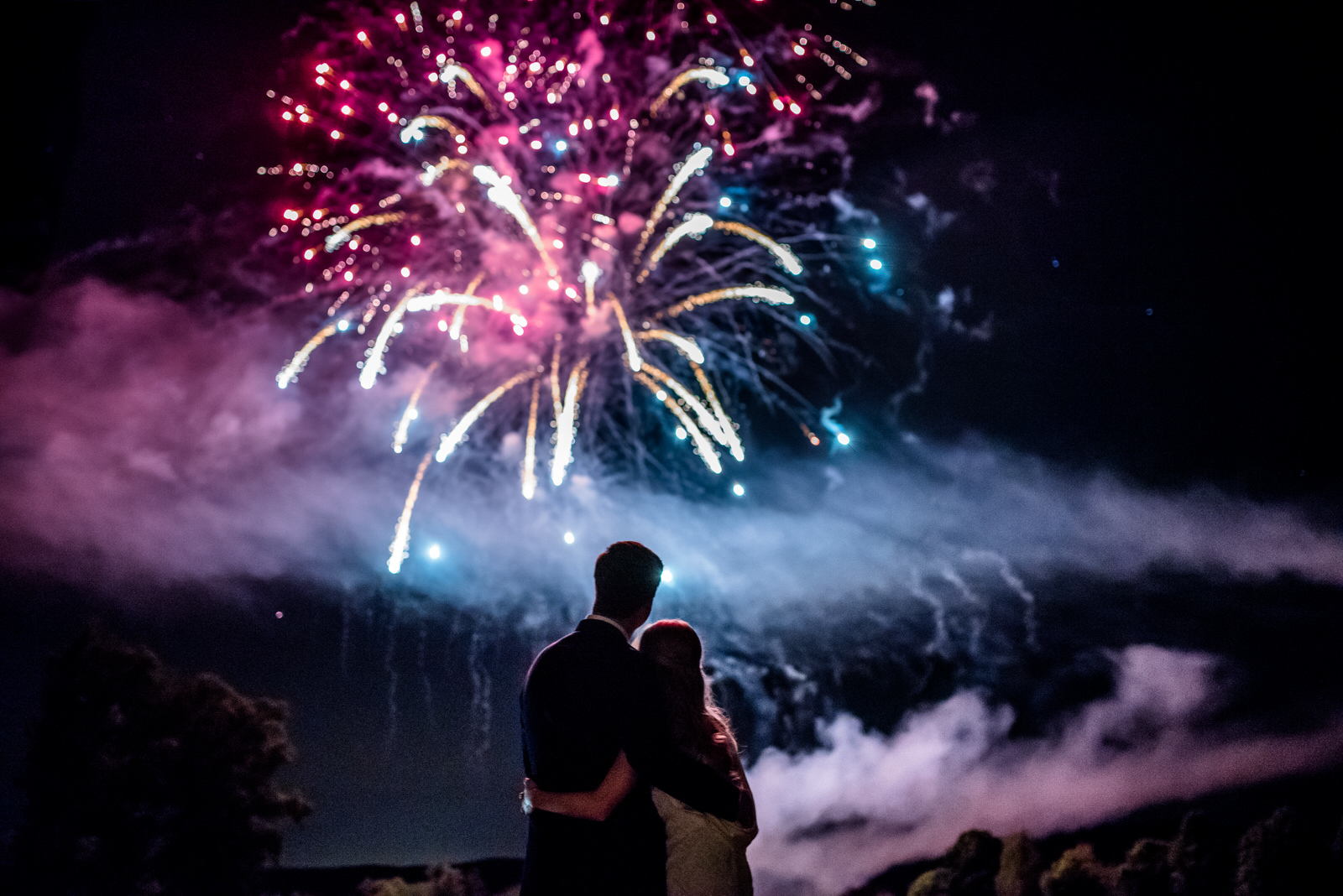 Fireworks display over bride and groom at the end of their countryside wedding