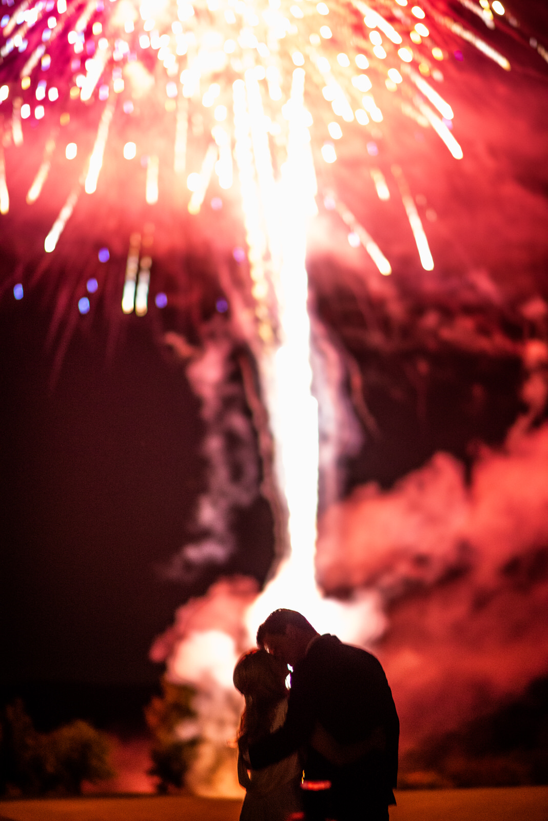 Bride and groom kissing under fireworks at wedding
