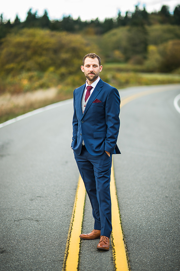Groom's portrait on road during a Whidbey Island wedding at Comforts Winery