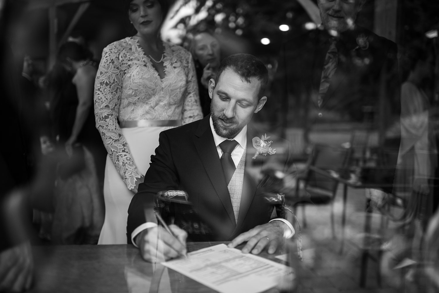 Groom signing the marriage certificate at a Whidbey Island wedding