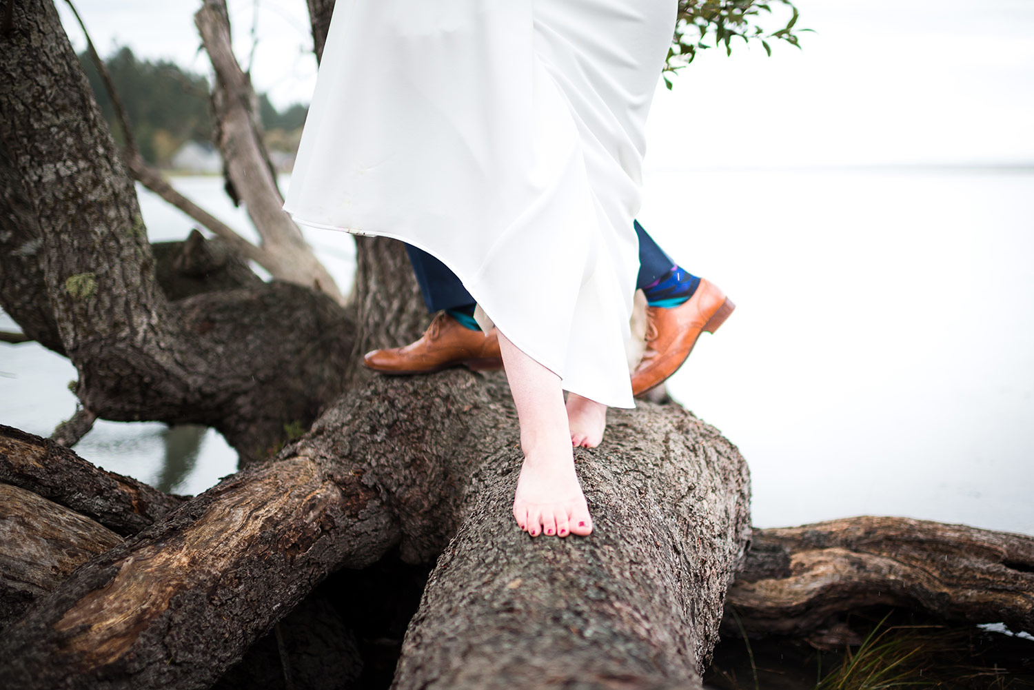 Bride walking barefoot during wedding portraits near water