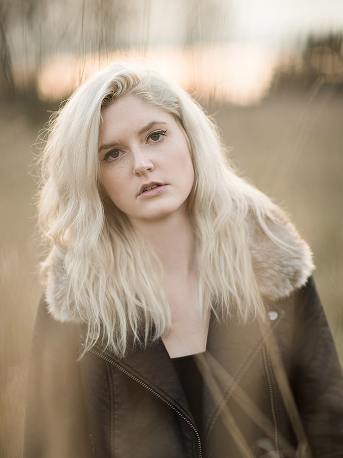 Fashion lifestyle model in Seattle at sunset in leather jacket with fur collar