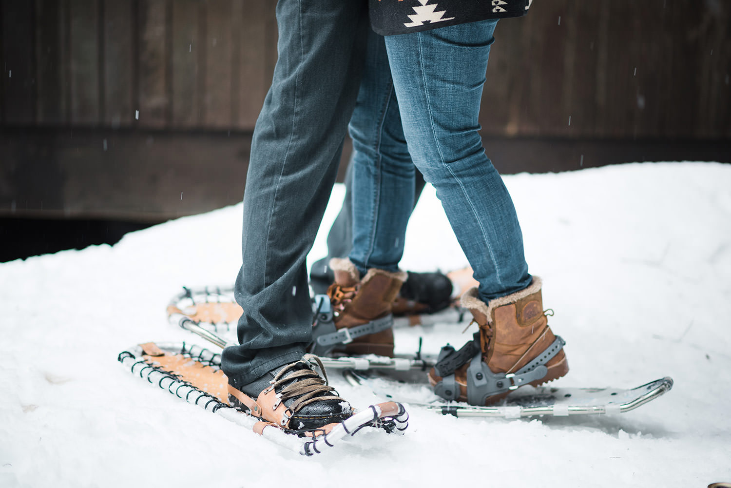 Couple wearing snowshoes for engagement session