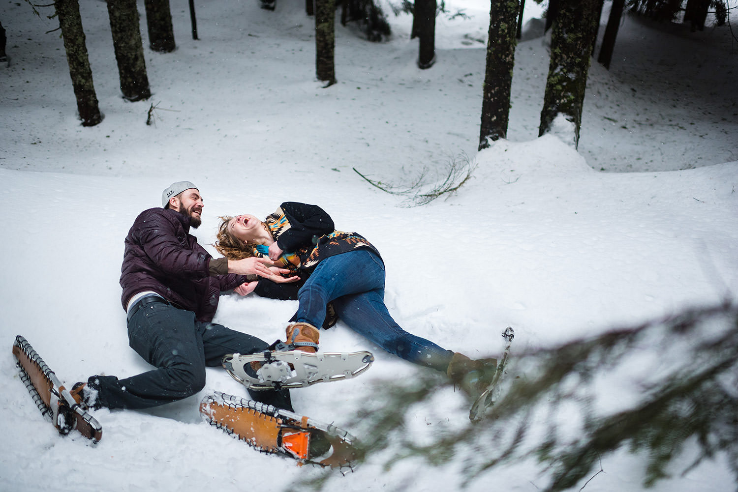 Laughing and falling in the snow on snowshoes for engagement session