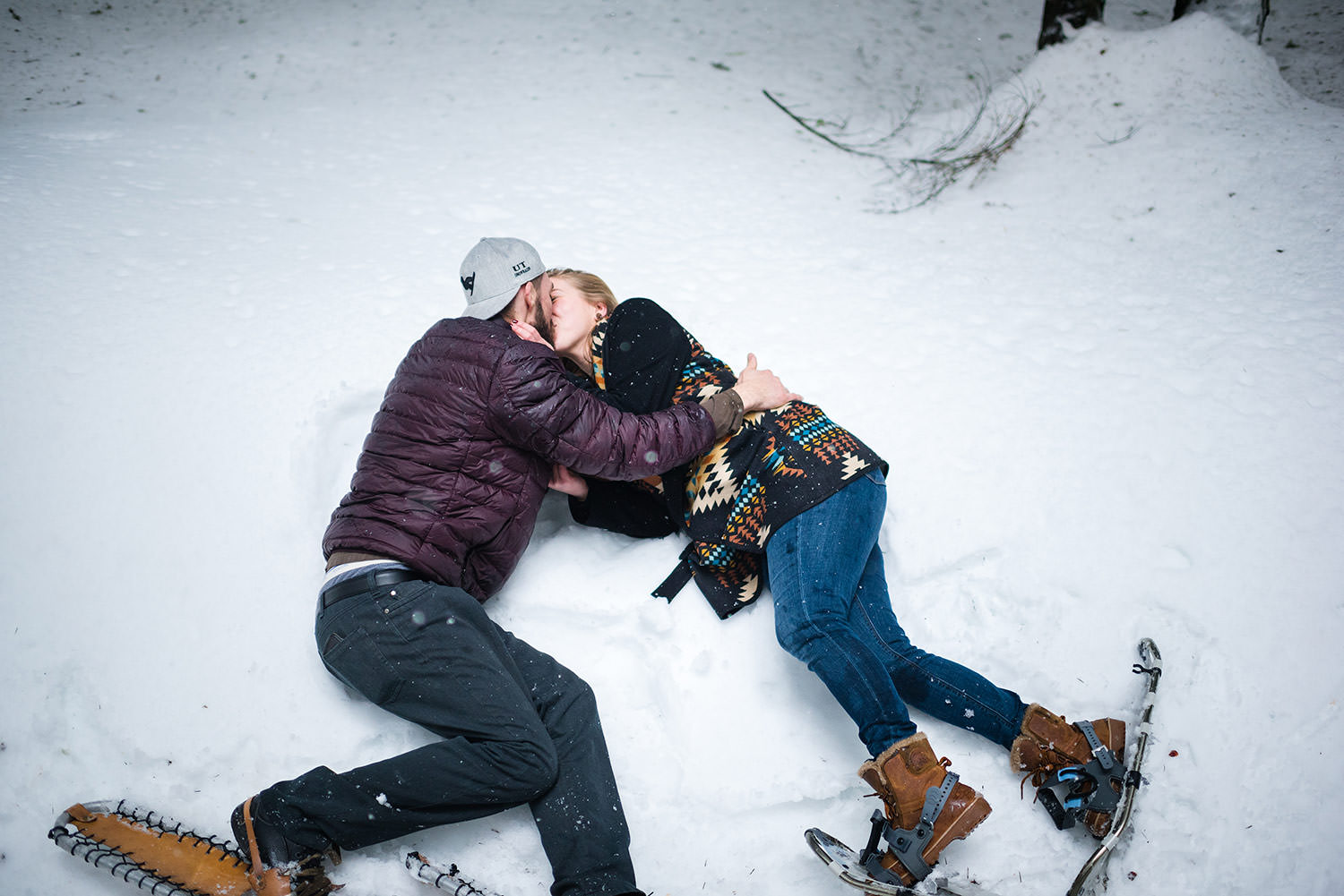 Laughing and kissing in the snow on snowshoes for engagement session