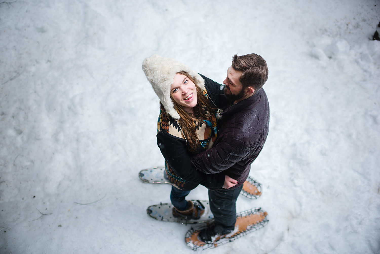 Couple laughing with snowshoes for engagement session