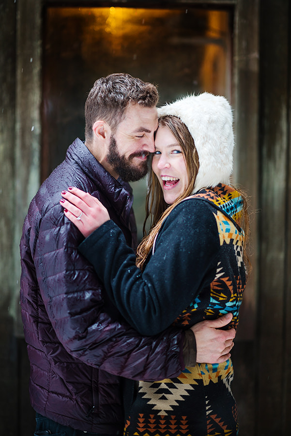 Laughing portrait of engagement session in front of cabin in the snow