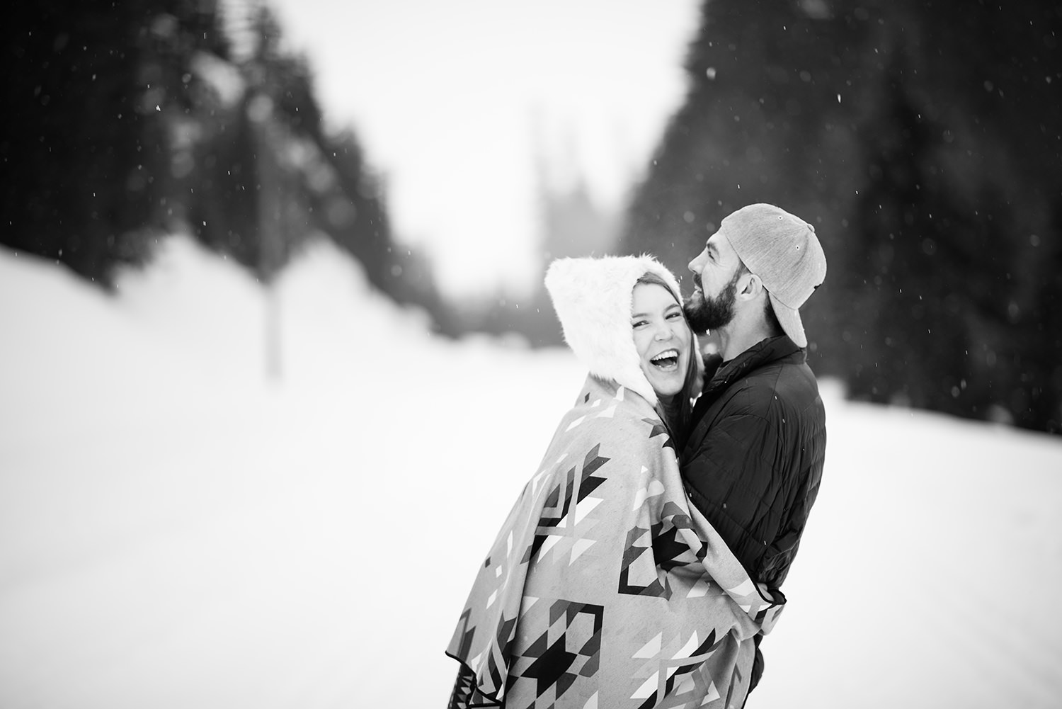 Engagement session wrapped in a blanket in the snow