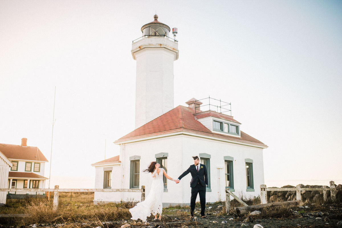 Bride and Groom in front of lighthouse on windy day