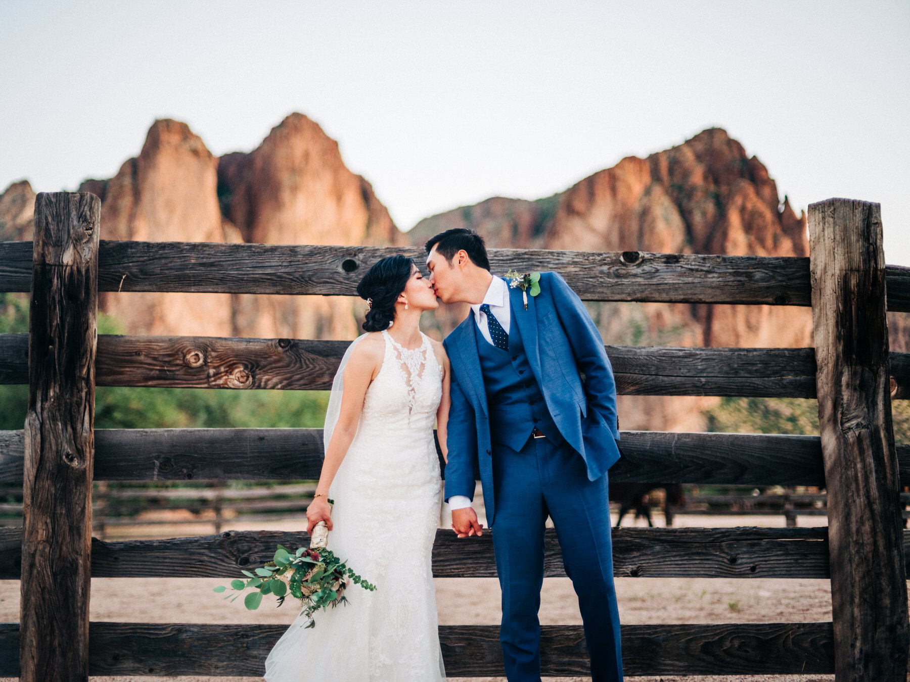 Saguaro Lake Ranch Wedding with horses behind bride and groom in stable