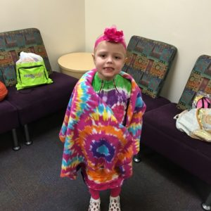 """""""Zoe loves her ComfyCozy shirts and wanted to wear them to school for show and tell. She tells everyone who asks about Amanda and even has her picture on the fridge. We see AHRA volunteers everywhere … painting children's nails in the clinic, feeding families every week, bringing gifts to inpatient children — and that's just at our hospital! They travel the Valley and beyond, helping families at other children's hospitals, too."""" -Vanessa and Pete Mellas"""