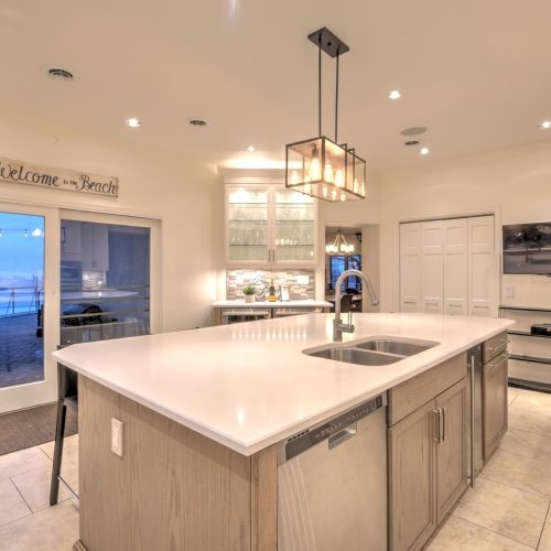 The Gourmet Kitchen features a large island in the center of the room, gas/electric ovens, two dishwashers, and a wine bar. Doors open up to the patio and a view of Lake Michigan.
