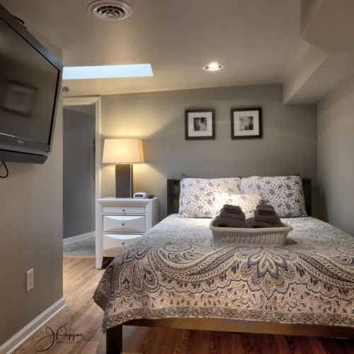 Interior view of a bedroom. A skylight allows sunlight to shine into the room. A large bed with a matching comforter and pillows is placed against the wall next to a white nightstand with a lamp on top. A flat screen television hangs on the wall to the left of the bed.