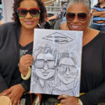Vacationing friends and holding their caricature by Ali.
