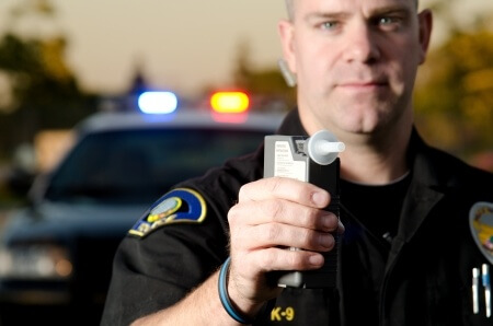 19225836 - a police officer holds the breath test machine for a suspect to blow into with a police car in the background