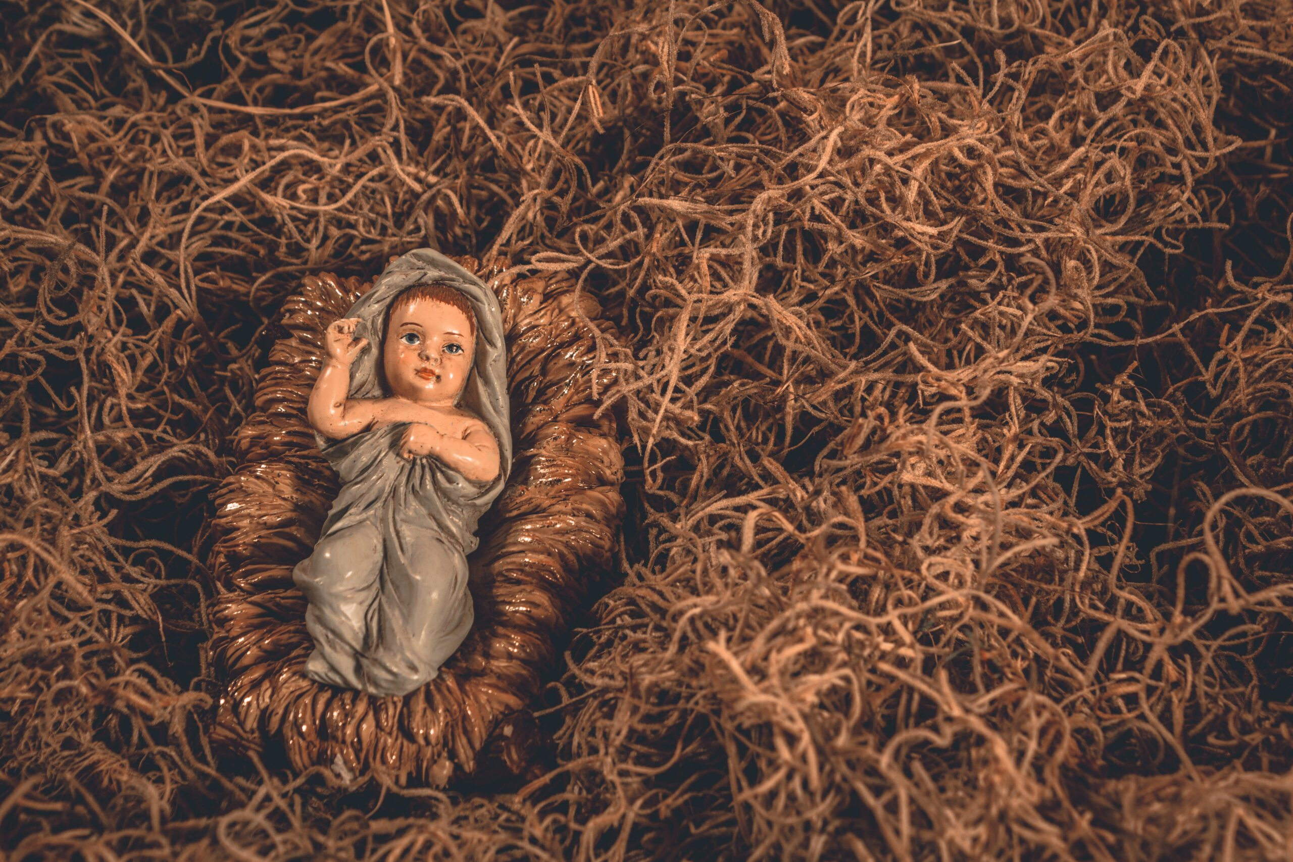Baby Jesus figurine from a nativity set laying in straw