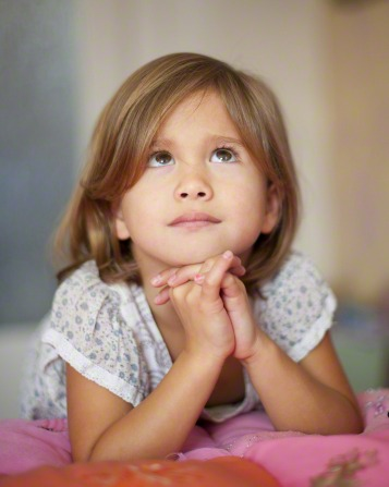 female child in nightgown kneeling at her bed with clasped hands under chin while looking up