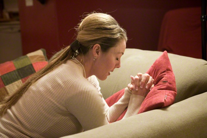woman praying on knees at tan stuffed chair with colorful pillows