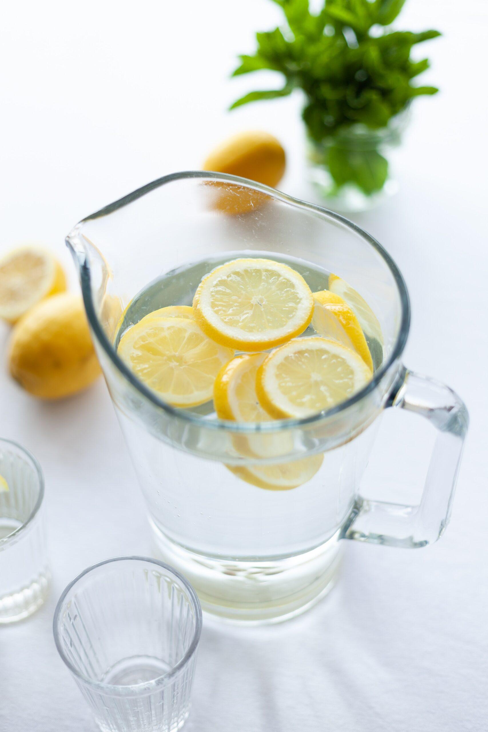 pitcher of lemonade with sliced lemons inside the pitcher and whole lemons outside the pitcher