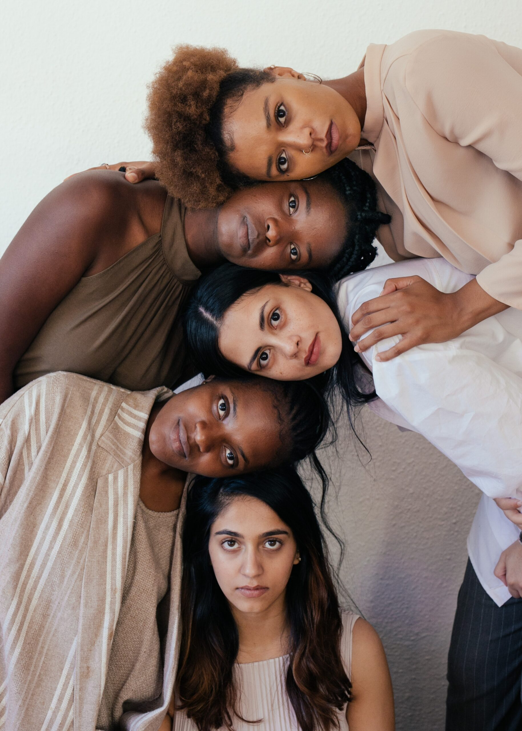 Five women from different cultures around the world touching heads on top of each other
