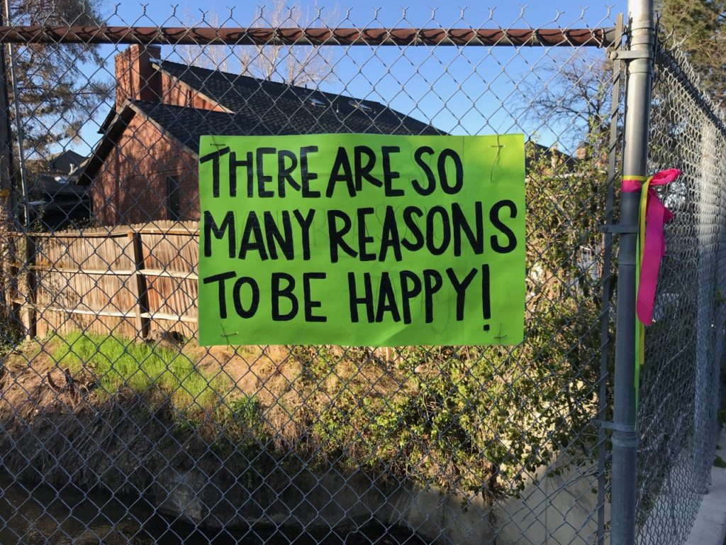 "sign attached to a chainlink fence that says, ""There are so many reasons to be happy!"""