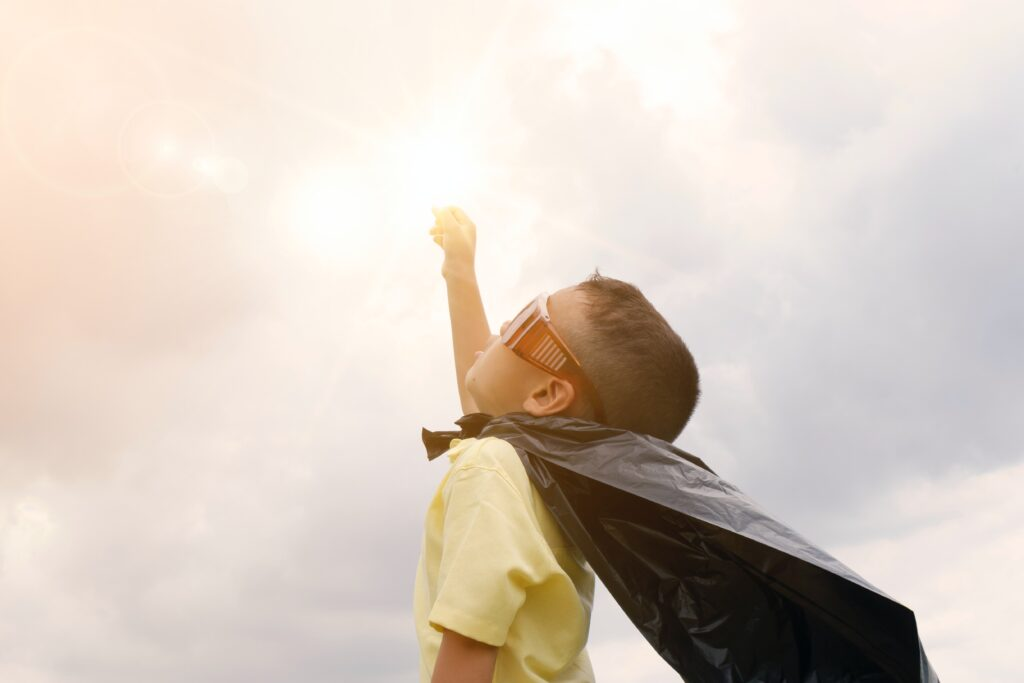Kid with superhero cape punching the sunshine