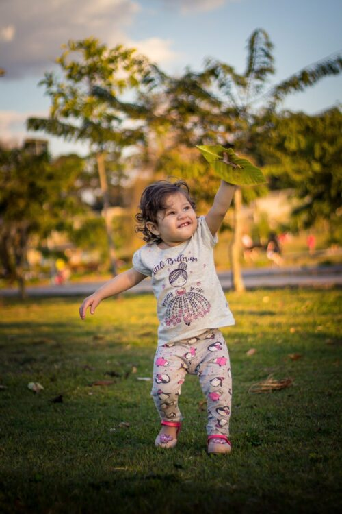 toddler with leaf playing on a grassy lawn