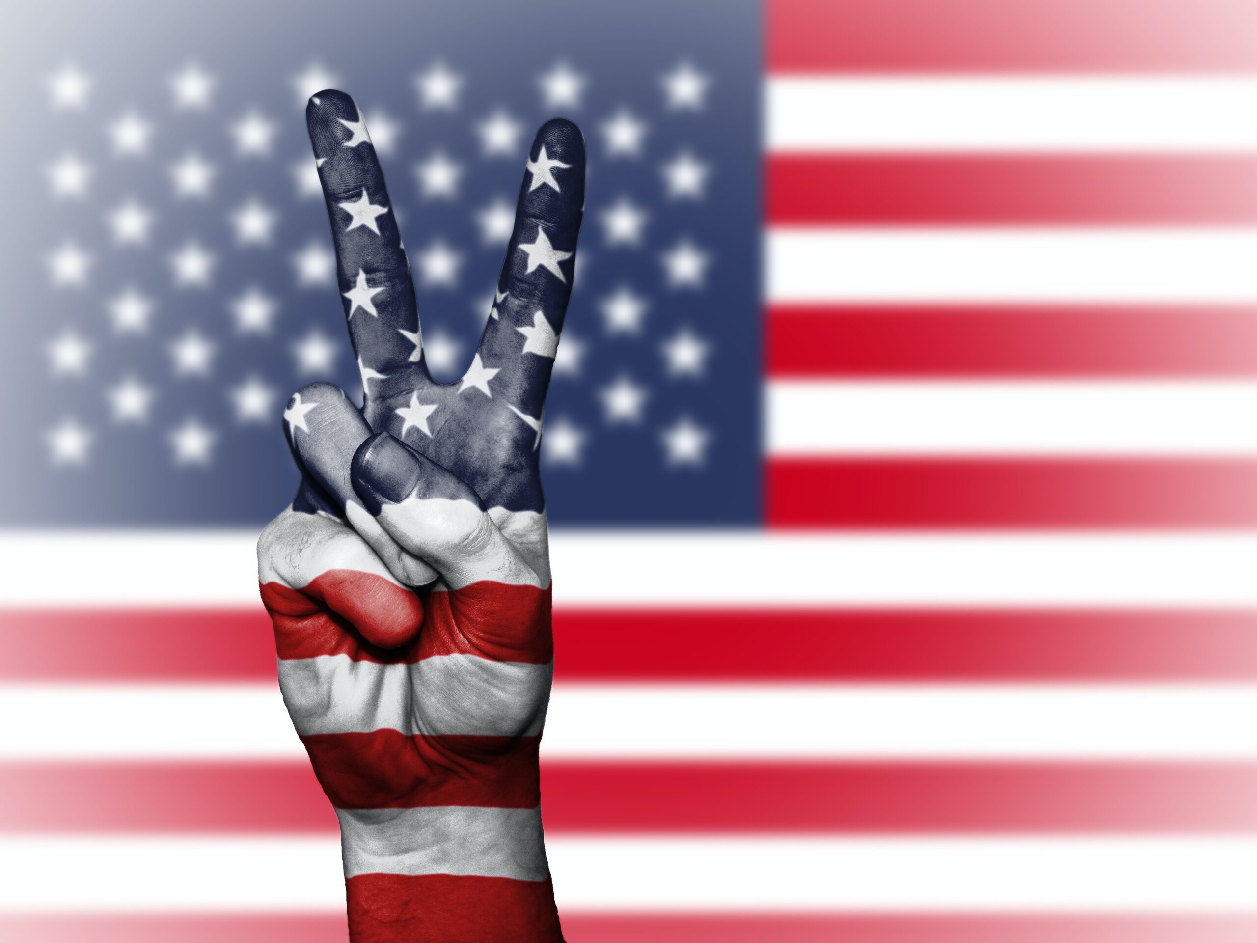 a person making the peace sign in front of an American flag