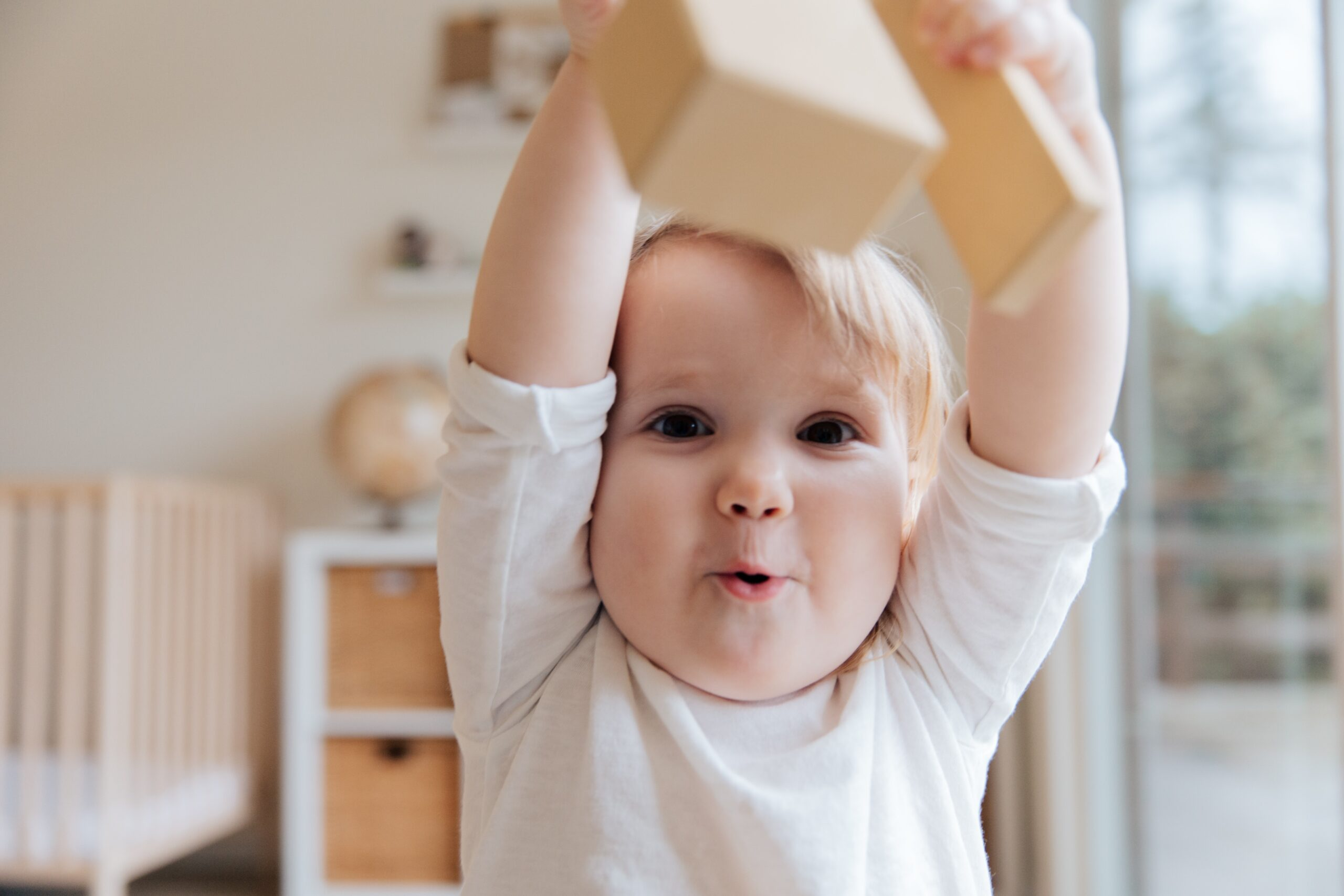 toddler lifting a block above his head